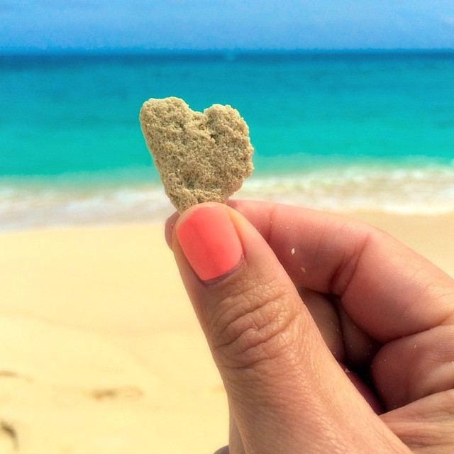 Girl holding Bermuda sand in the shape of a heart