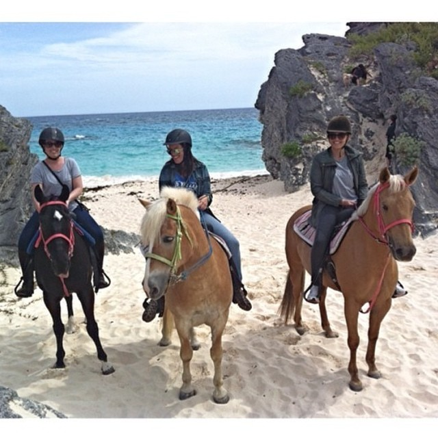 Tourists riding horses on a beautiful Bermuda beach