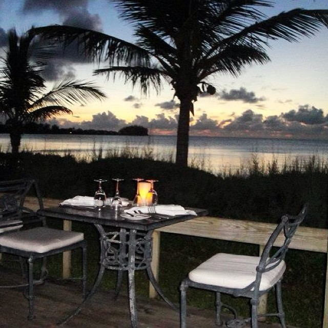 Dining on the beach at sunset at Breezes restaurant at Cambridge Beaches