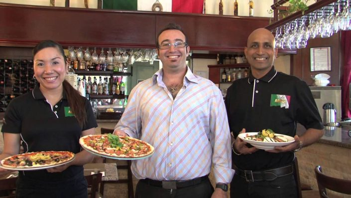 Cafe Amici waiter holding best pizza in Bermuda