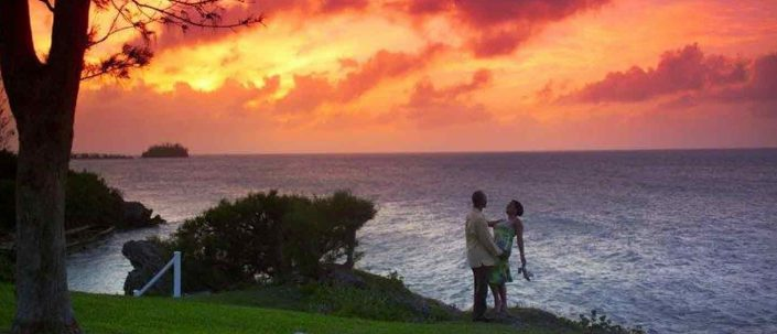 Best of Bermuda slider image of romantic couple watching sunset over bermuda ocean at Cambridge Beaches Resort and Spa