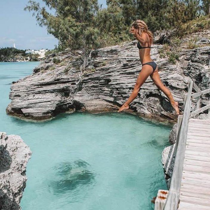 girl in bikini jumping from bridge into blue bermuda ocean